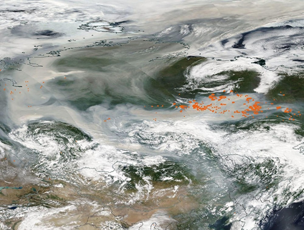 Satellite image taken by NASA shows a Siberian forest fire, with smoke so dense it practically blurs the ground.