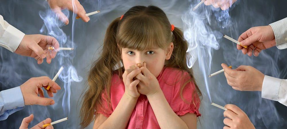 criança tampa o nariz para fugir do cheiro do cigarro