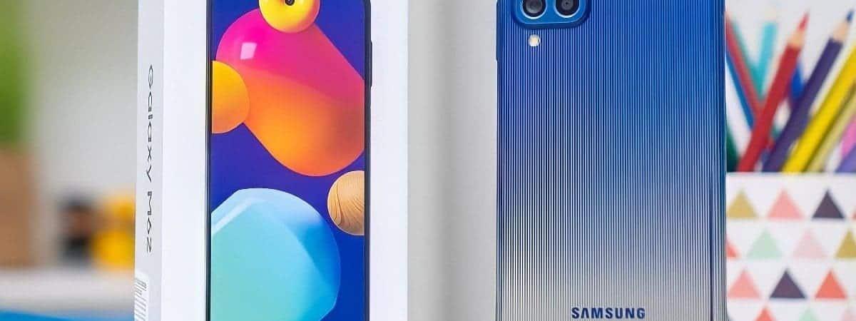 Imagem mostra o Samsung Galaxy M62 ao lado de sua caixa original. O aparelho evidencia as quatro câmeras traseiras e a sua cor azul