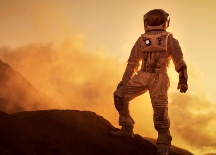 Imagem conceitual mostra um astronauta caminhando por região montanhosa de Marte