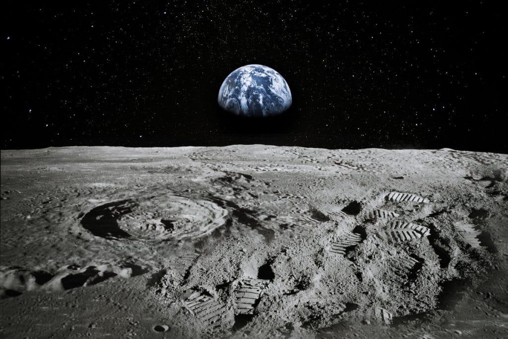 Imagem mostra a superfície da Lua, com a Terra vista ao fundo. Novo estudo da Nasa argumenta que a Lua pode esconder água nas sombras de suas crateras