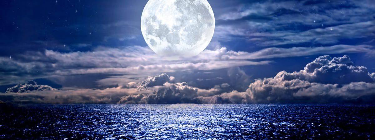 Imagem mostra a lua por trás de algumas nuvens, e o mar refletindo a sua luz no pé da foto