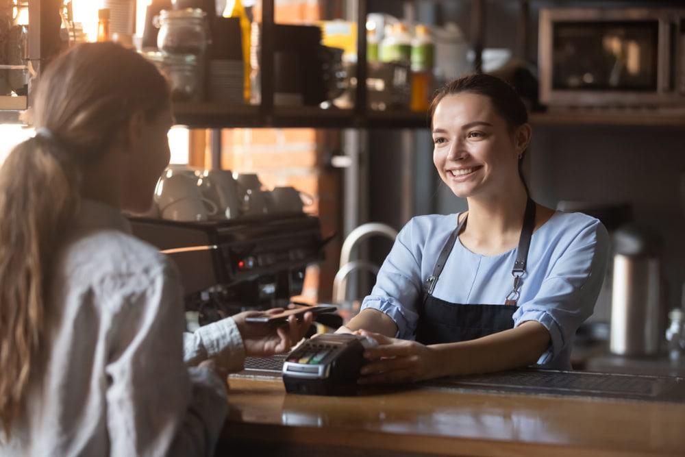 Cliente segurando um smartphone e realizando um pagamento digital com a vendedora no balcão de uma loja