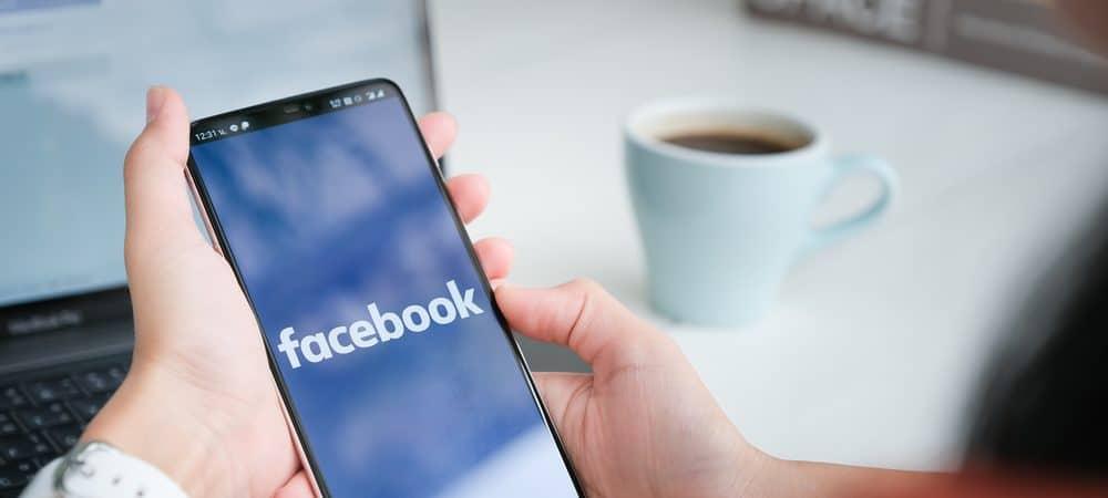 Uma mulher segura um celular com o aplicativo do Facebook na tela
