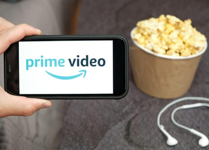 Homem segurando um smartphone com o logotipo do Amazon Prime Video e uma caixa de pipoca ao lado