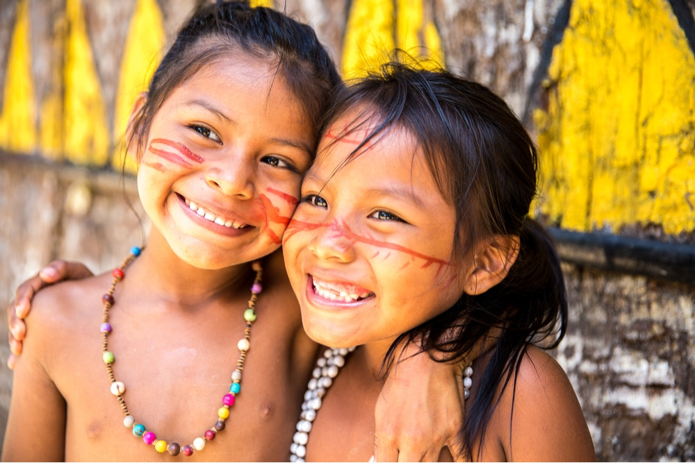 Imagem mostra duas crianças indígenas sorridentes e abraçadas, com pinturas faciais e vestimentas nativas em evidência