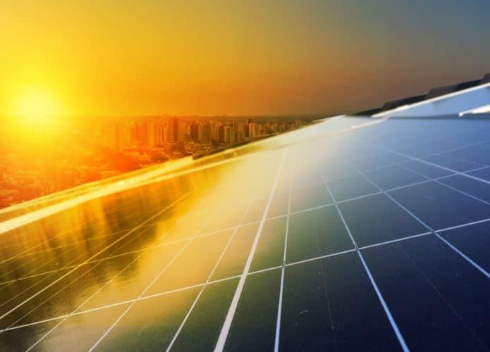 La imagen muestra el sol brillando debajo de las células de energía fotovoltaica