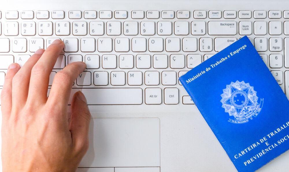 mão em cima do teclado com carteira de trabalho ao lado