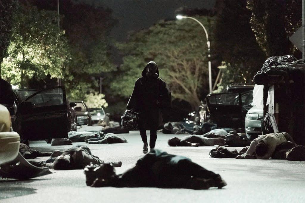 Foto mostra personagem utilizando capa e máscara de proteção biológica enquanto caminha por rua escura repleta de corpos pelo chão.