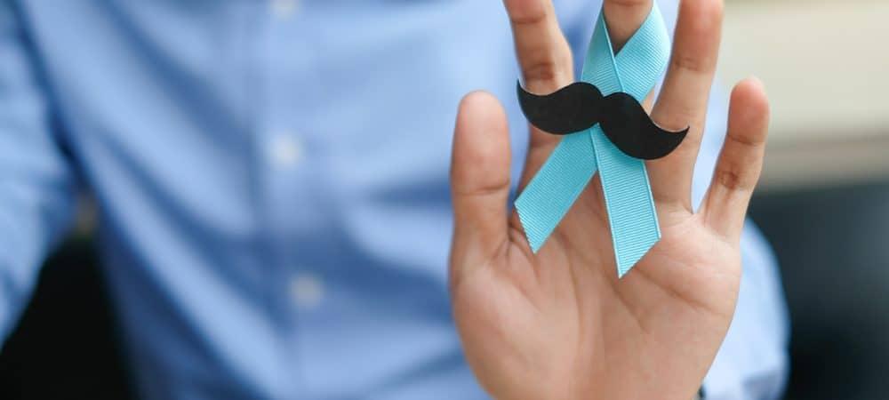 Homem segurando um laço azul com bigodes