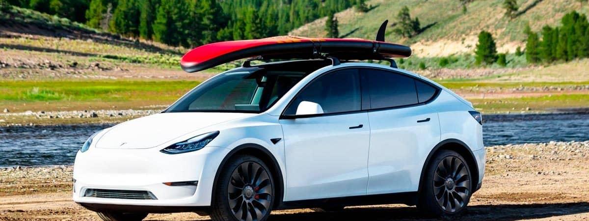 carro Tesla Y performance com prancha de surf estacionado em ambiente de natureza