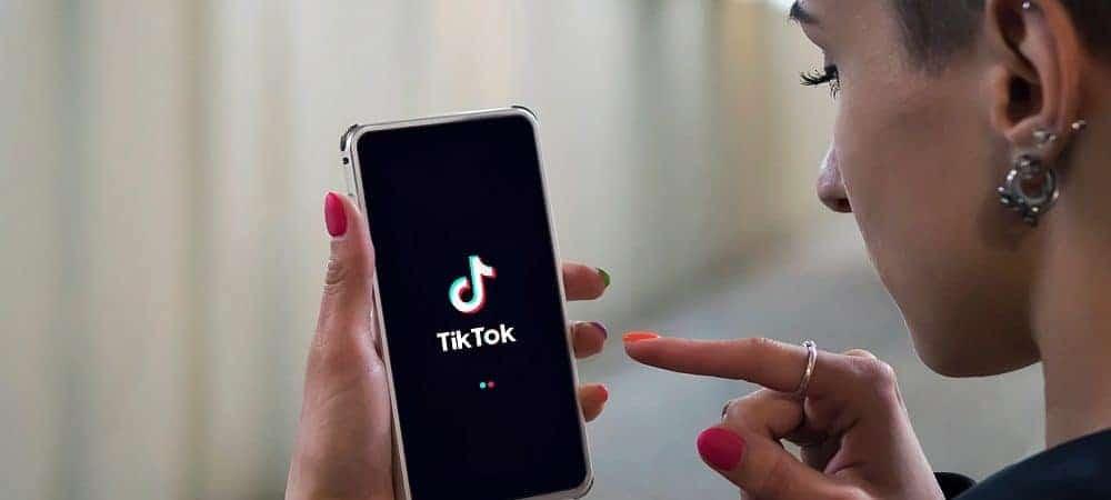 Mulher segurando celular e mostrando o aplicativo do TikTok.