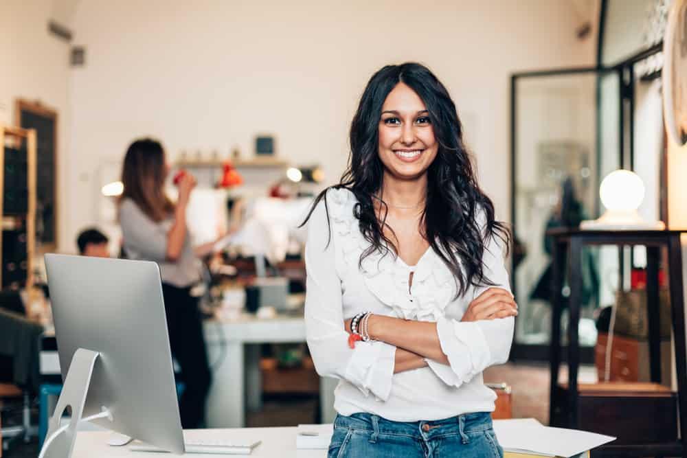 Mulher sentada ao lado de uma tela de computador com outras pessoas desfocadas no fundo