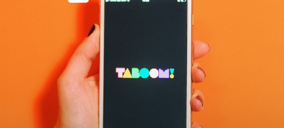 mão feminina segurando celular com logo Taboom