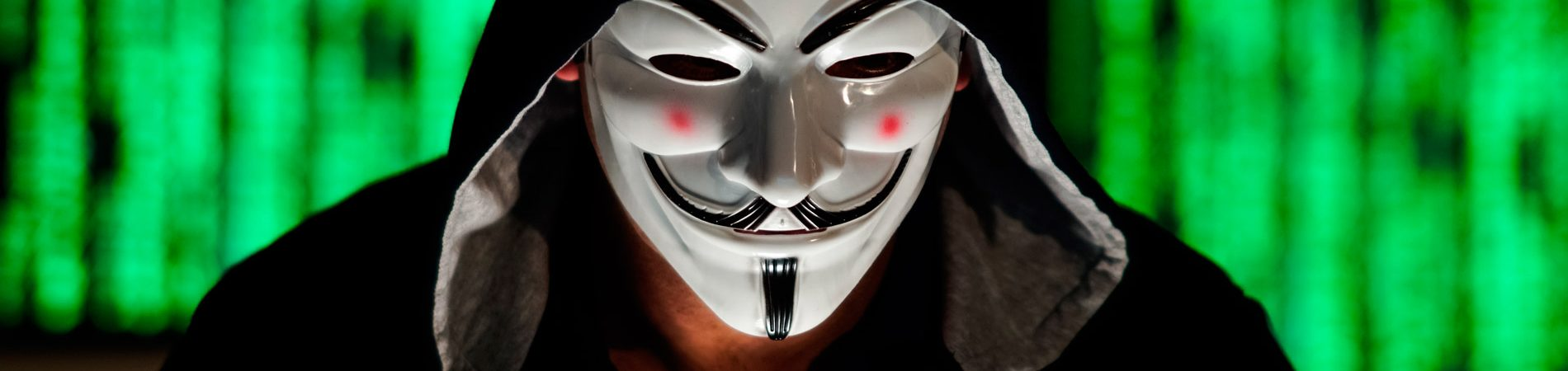 hacker with V for Vendetta mask in front of computer