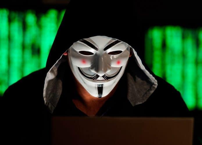 hacker com mascara do V de Vingança na frente do computador
