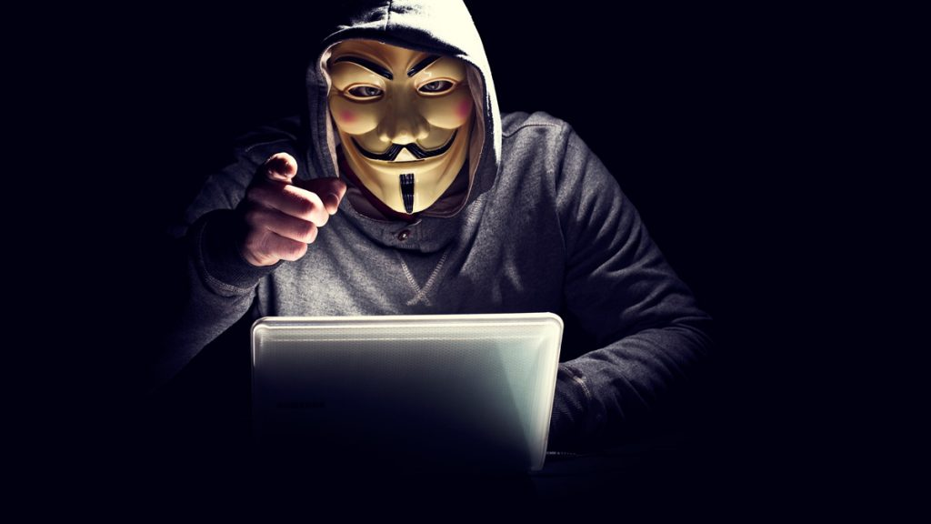 hacker with anonymous group mask pointing at you