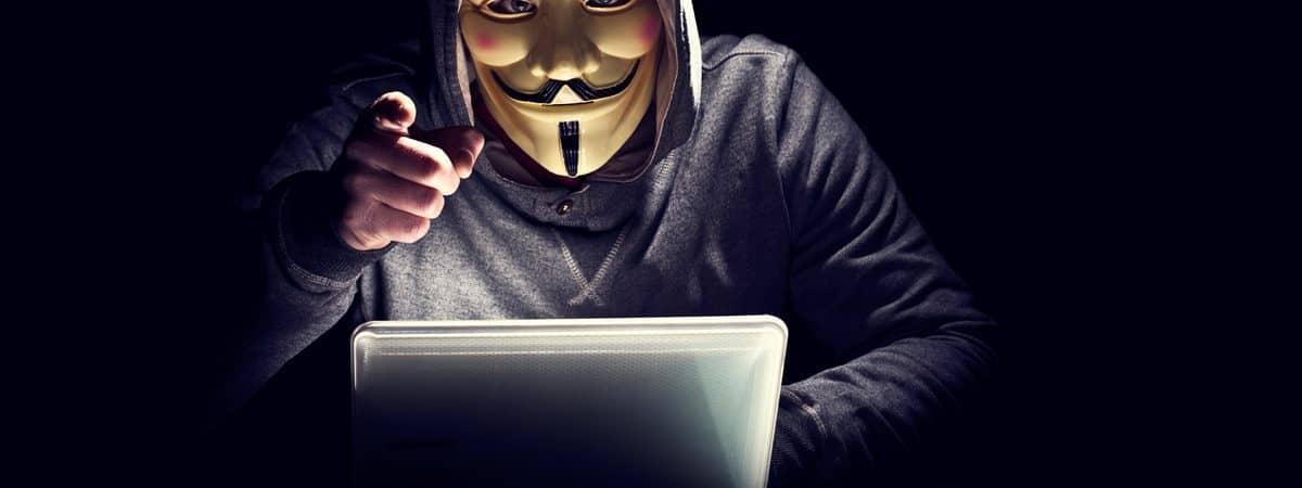 hacker com mascara do grupo anonymous apontando para você