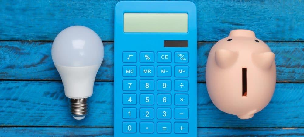 Imagem ilustra a economia de energia elétrica com um lâmpada LED, uma calculadora e um cofrinho