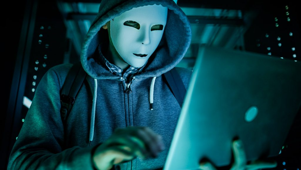 hacker with mask and hoodie typing on notebook