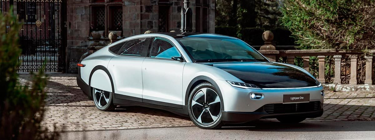 versão comercial do lightyear one, carro estacionado na rua em frente a garagem