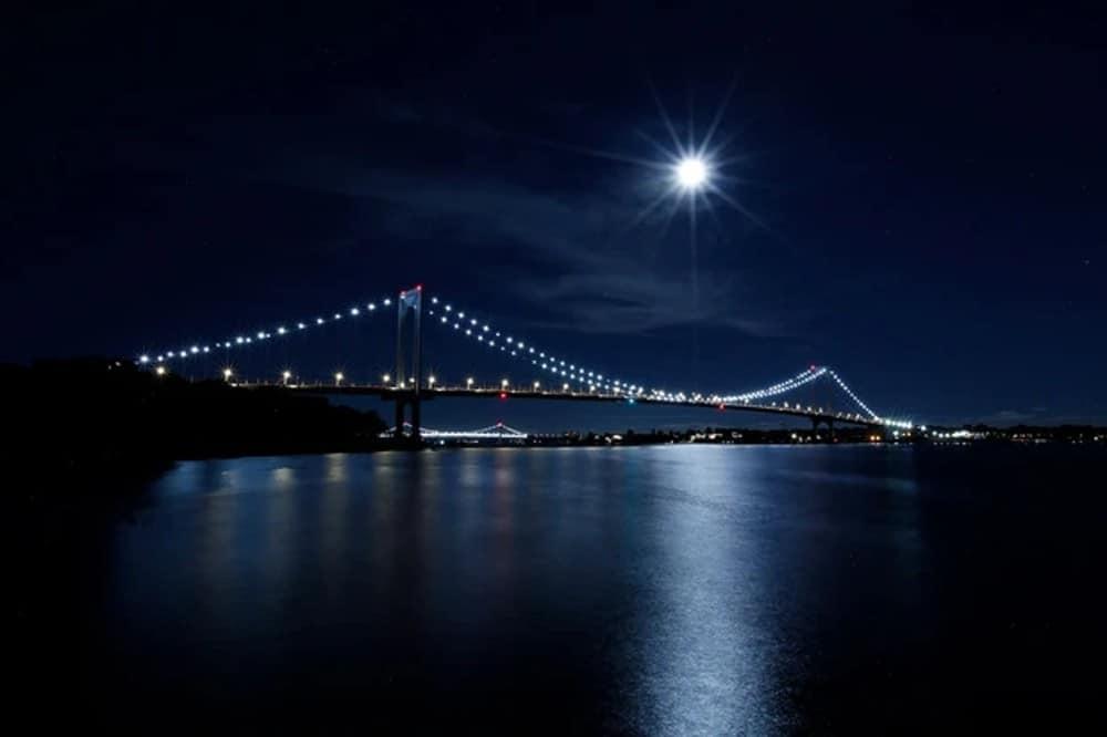 Foto da Ilha da Colheita se mostrando no alto, por trás de uma ponte em área urbana
