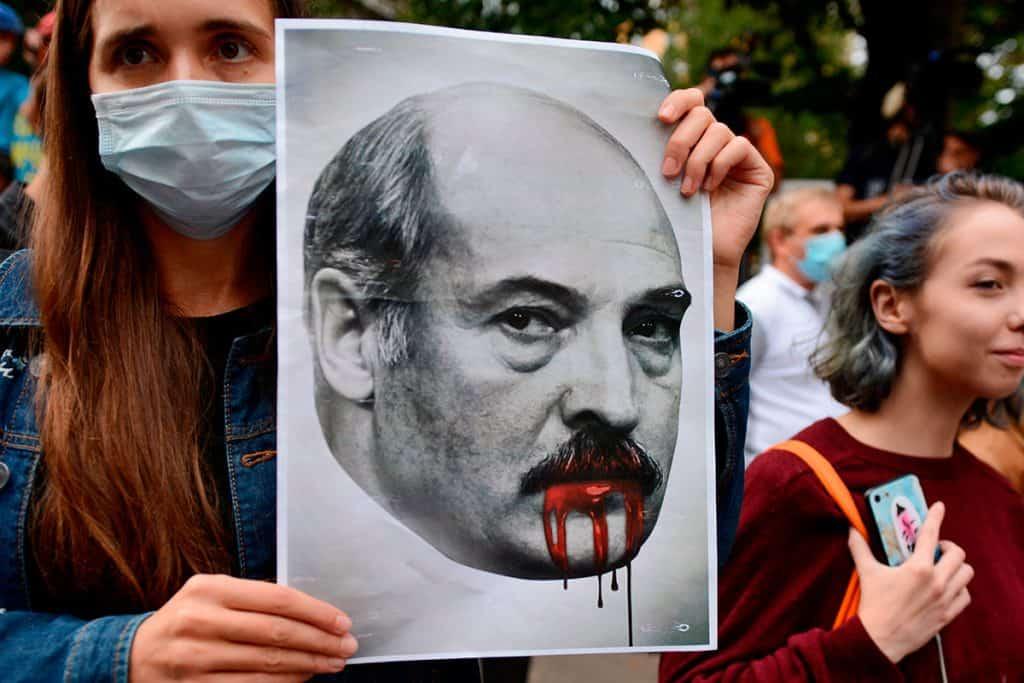 manifestante segurando cartaz com a boca de Lukashenko derramando sangue