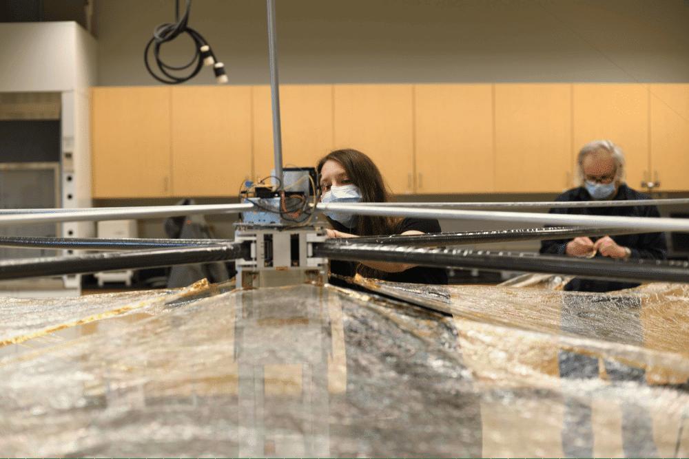 Imagem mostra cientistas trabalhando no Spinnaker3, um dispositivo que arrasta naves de sua órbita para uma posição de reentrada mais segura