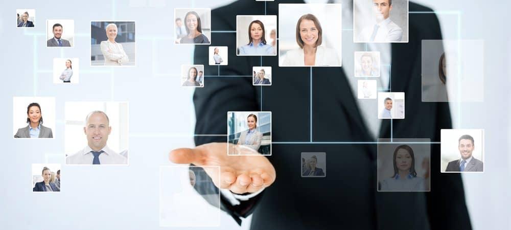 Imagem mostra o torço de um homem com traje formal e a mão direita levantada com a palma para cima; à frente, pode-se ver diversas fotos 3x4 digitalizadas, de pessoas, como se o homem estivesse usando uma tecnologia para selecionar uma dessas pessoas