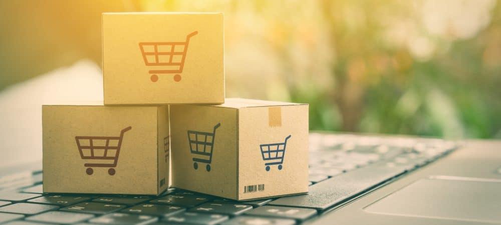 Conceito de comércio eletrônico com caixas e um carrinho de compras em um teclado de laptop. Imagem ilustra clientes encomendando produtos de sites de varejistas através da internet.