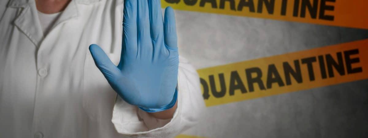 Imagem mostra a mão de um médico impedindo a passagem de uma pessoa, com faixas de passagem proibida atrás dele
