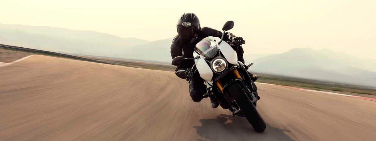motorista inclinado na moto dirigindo em alta velocidade
