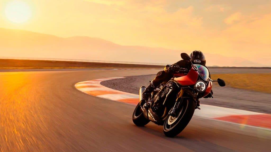 motorista inclinado na moto dirigindo em alta velocidade no fim de tarde