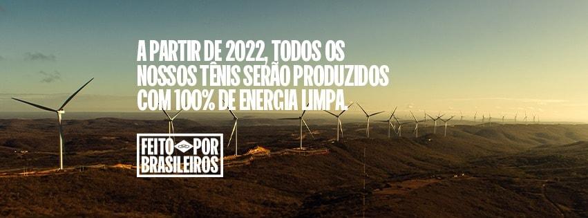 """Imagem mostra ao fundo gerador de energia eólica. Pode se ler a frase: """"a partir de 2022, todos os nossos tênis serão produzidos com 100% energia limpa"""", divulgação da Vulcabras para a marca Olympikus"""
