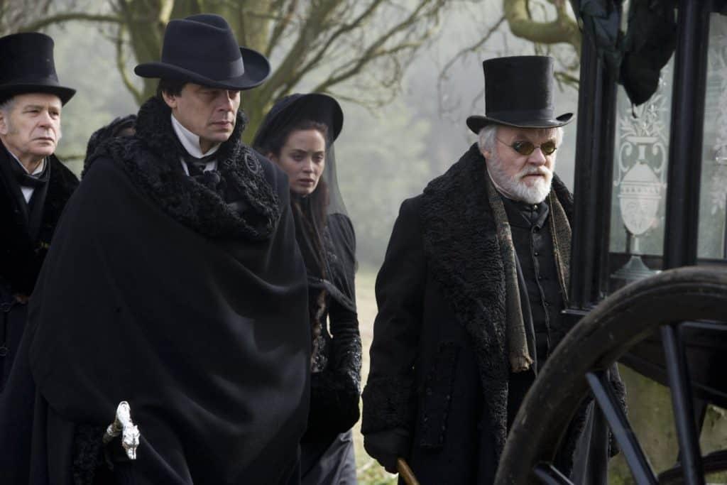Benicio del Toro, Anthony Hopkins e Emily Blunt no funeral do responsável pelo financeiro de 'O Lobisomem'. Imagem: Universal Pictures/Divulgação