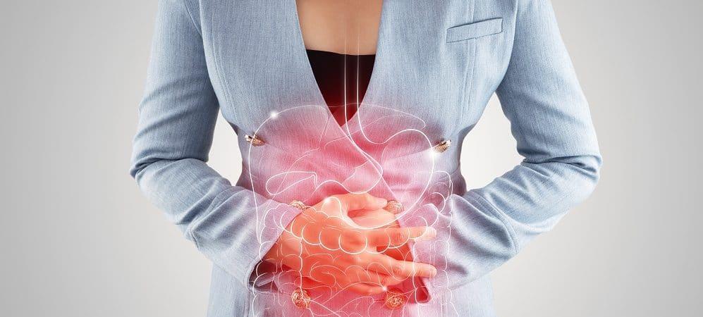 mulher com a mão no estômago sinalizando câncer de cólon