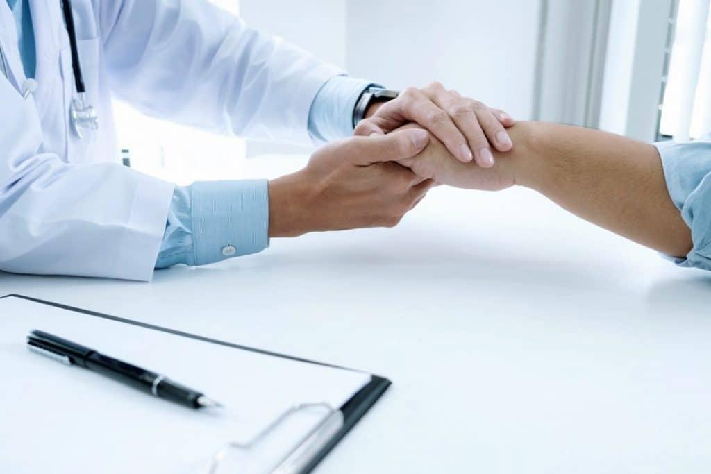 Médico com a mão sobre a mão do paciente