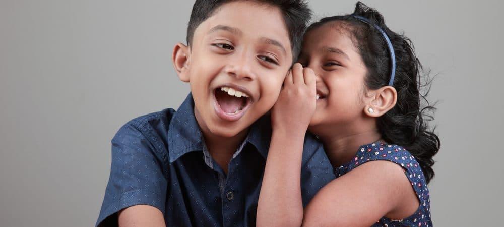 Uma menina conta uma piada para um menino