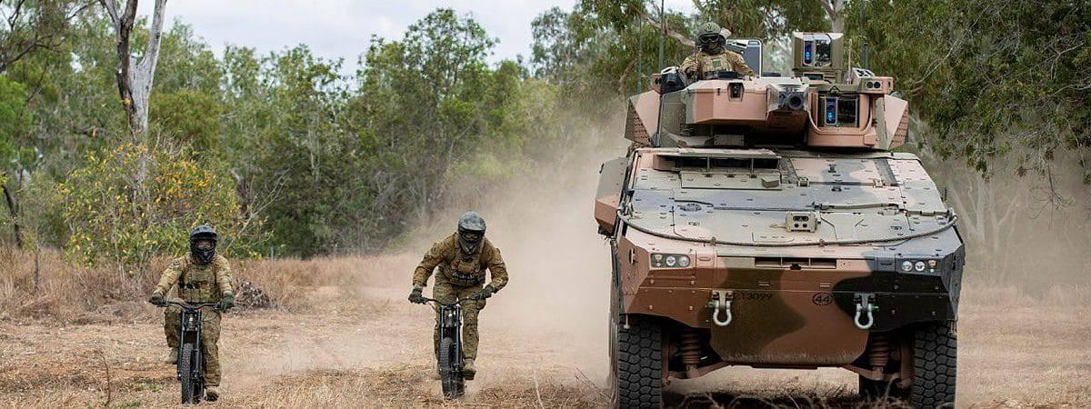 duas e-bikes da Stealth com um blindado rodando ao lado
