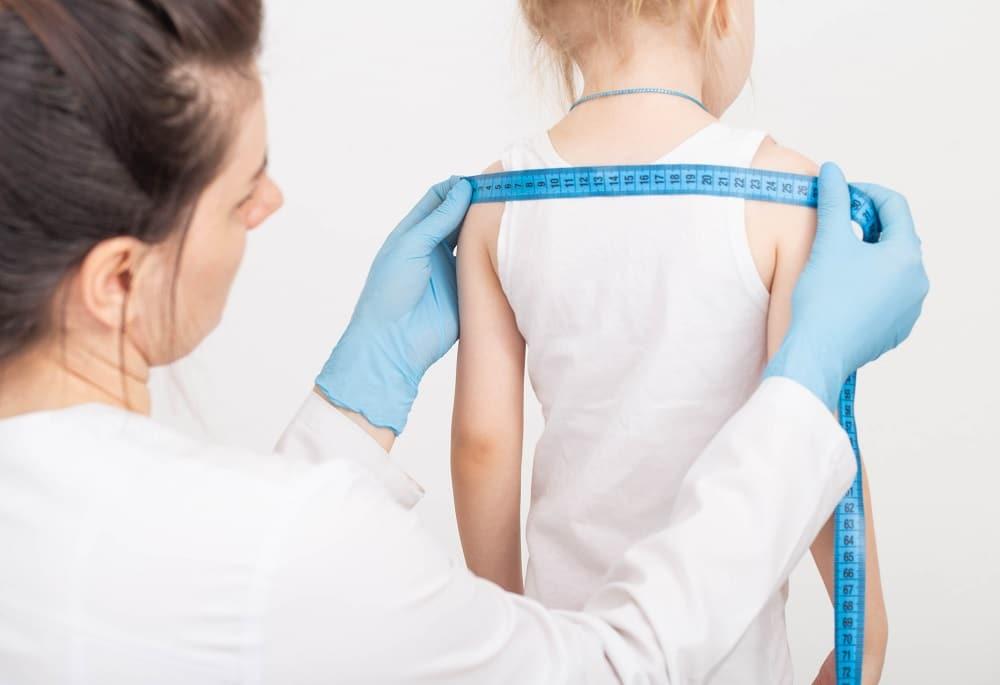 médica medindo crescimento de criança com fita