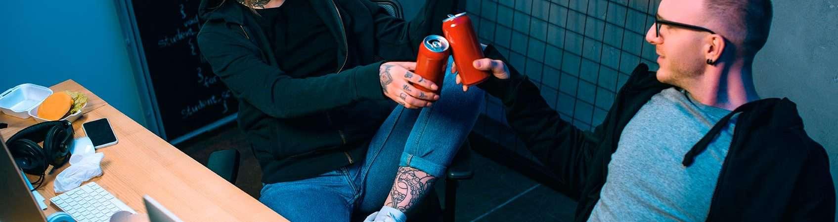 hackers brindando com duas latas de cerveja na frente de computadores