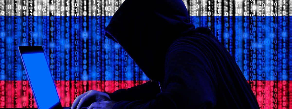 hacker de capuz digitando em teclado com letras sobrepondo ele e formando a bandeira da rússia