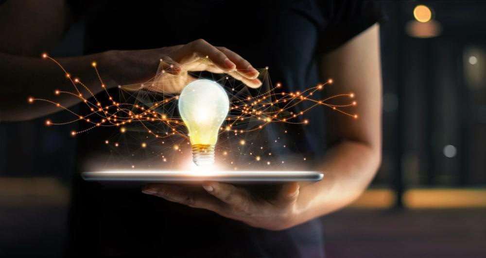 Imagem mostra uma mão feminina segurando uma superfície reta, em cima dessa superfície está uma lâmpada acessa, representando uma ideia de inovação