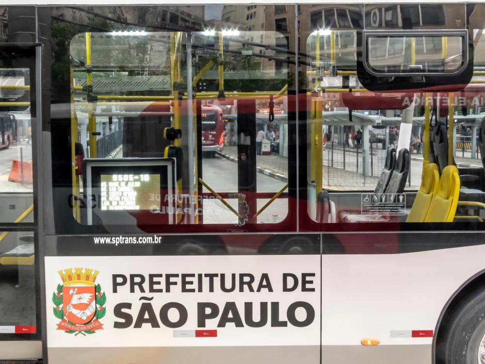 Imagem mostra a lateral externa de um ônibus da capital paulista, adesivado com os dizeres Prefeitura de São Paulo e o brasão da prefeitura.