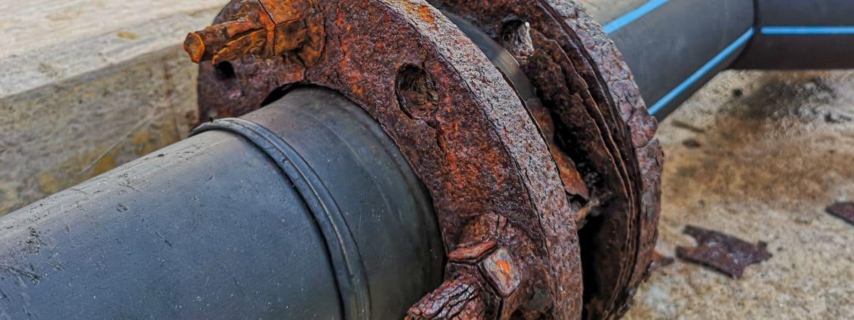 Foto mostra um cano de zona portuária enferrujado, simbolizando a poluição por metais