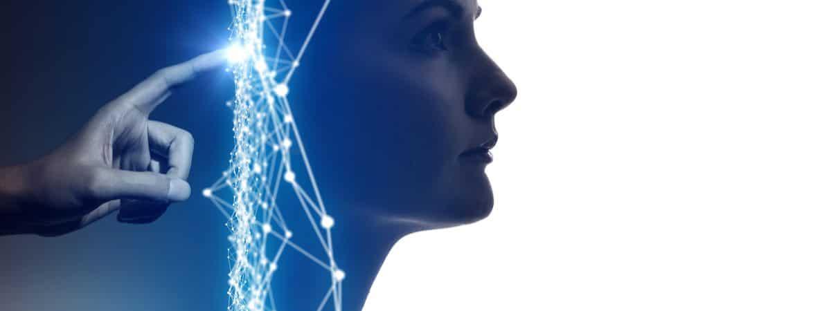 Imagem conceitual mostra uma mão tocando com o indicador a parte de trás da cabeça de uma mulher, com traços digitais azuis entre um e outro. A ideia é simbolizar a inteligência artificial