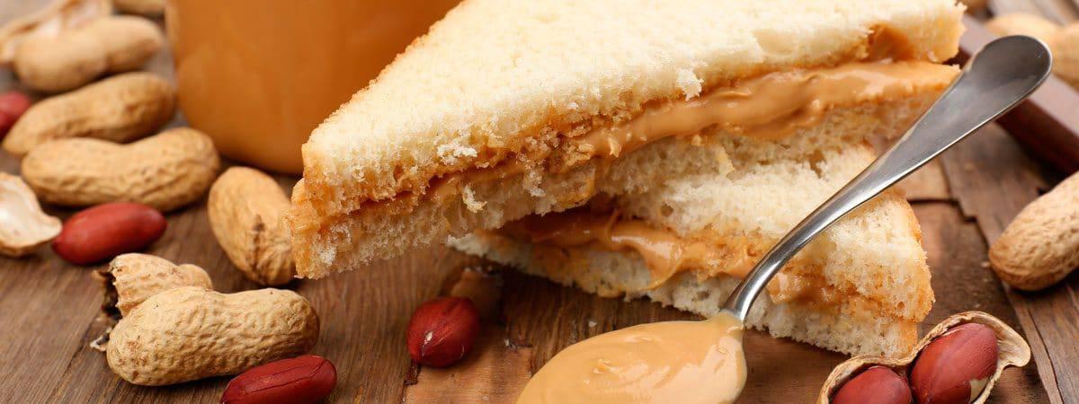 duas metades de sanduíche de pasta de amendoim em mesa de madeira rodeado de amendoim
