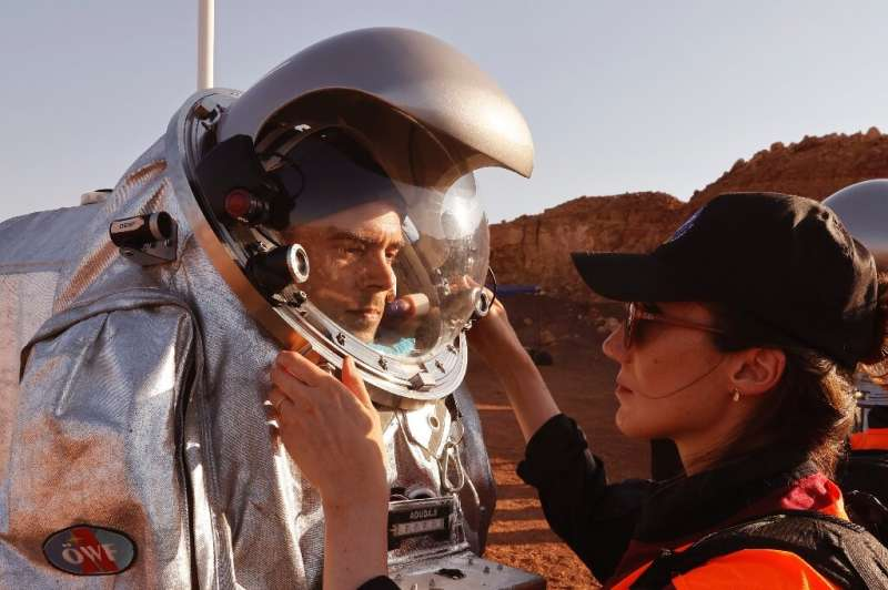 Técnicos ajudam a ajustar traje de astronauta em projeto que simula a vida em Marte dentro de Israel